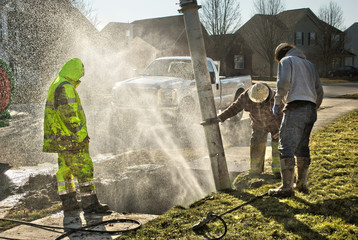 Muddy utility worker men fixing broken water line with droplets spraying into the air.