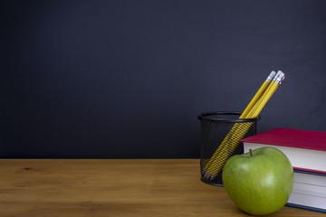 manzana  verde con  libros con lápices y pizarra vacía, regreso a la escuela