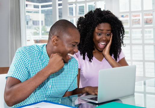African american couple shopping presents and gifts online with laptop