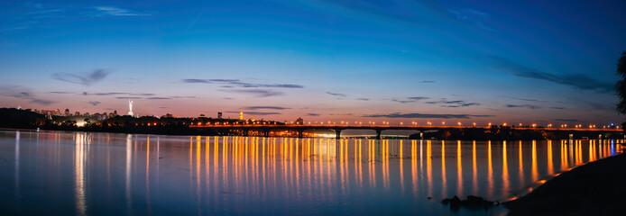 Panorama of Kiev city at night. Kyiv Left bank skyline with Paton bridge over Dnieper river.