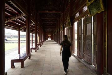 Junge Frau in Laubengang im Kaiserpalast in Huế, Vietnam
