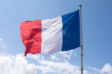 French Tricolour flag blowing in the wind on a blue sky day