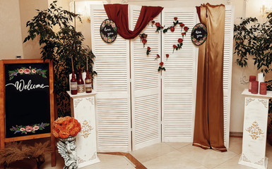 wedding photo booth zone and welcome board. rustic wooden wall with flowers, red roses heart and love signs, decorated backdrop and empty chalkboard. wedding reception and ceremony