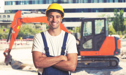 Red earthmover with strong latin american construction worker