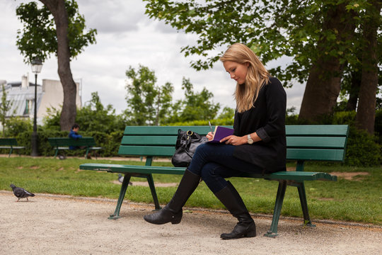 Beautiful Young Woman Sitting on Park Bench, Writing in a Journal