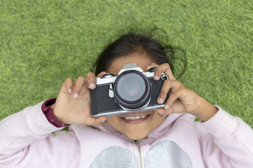 Cute little girl taking pictures with her vintage camera