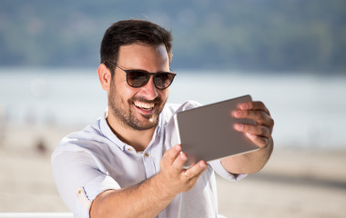 Man with tablet enjoying beside river