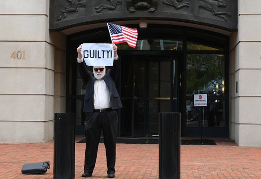 After a guilty verdict on the first count, an unidentified man holds a sign outside the U.S. District Courthouse for the fourth day of jury deliberations in former Trump campaign manager Paul Manafort's trial