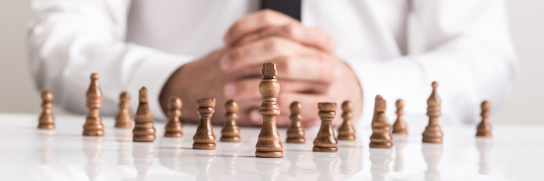 Businessman planning strategy with chess figures on white table