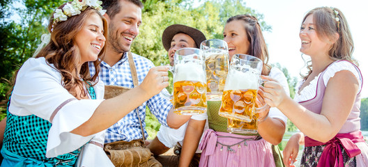 Freunde Trinken Bier in der Bayerischer Tracht an der Isar