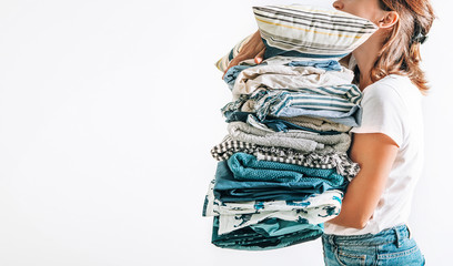 Woman takes in hands big pile blue and beige blankets, towels and other home textile