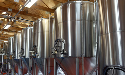Row of shiny metal micro brewery tanks.