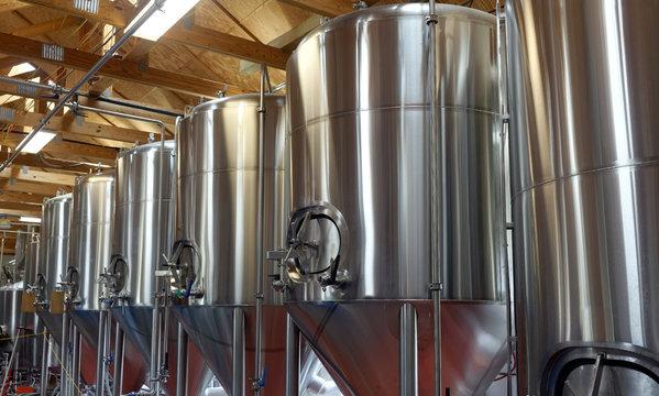 Row of shiny metal micro brewery tanks.