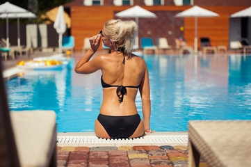 Beautiful blonde woman posing near swiming pool