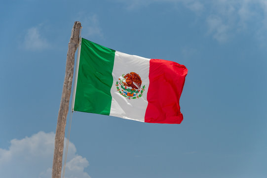Mexican flag over blue sky in Tulum, Mexico.