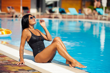 Beautiful woman relaxing by the pool