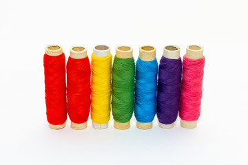 Standing colored thread coils on white background