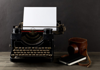 Vintage typewriter with empty, blank sheet of paper, camera and notebook on wood table
