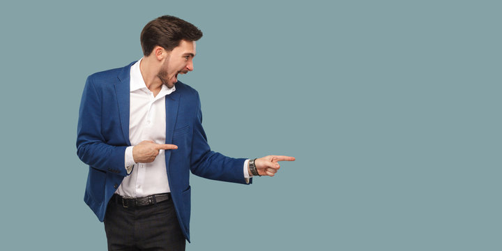 Handsome amazed bearded man in blue suit standing and pointing at background and screaming and looking at copy space.