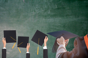 Graduation holds a black hat and a yellow tassel,The backdrop is a blackboard.