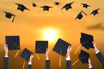 Graduation holds a black hat and a yellow tassel on sunset background.