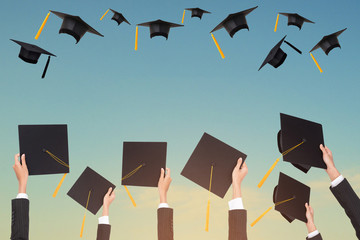 Graduation holds a black hat and a yellow tassel on blue sky background.