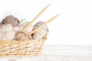 Neutral beige yarn in a wicker basket. White background. Aged wood. Needles, scissors.