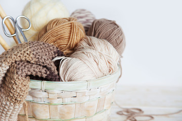 Neutral beige, brown, white yarn in a wicker basket. White background. Aged wood. Needles, scissors.