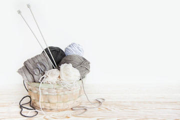 Neutral grey and white yarn in a wicker basket. White background. Aged wood. Needles, scissors.