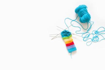 Colored rainbow children's socks. Bright yarn. White background. Knitting with knitting needles.