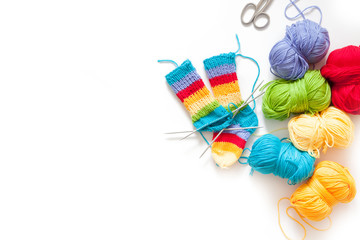 Knitting for children. Bright striped rainbow socks. Colored yarn. White background.