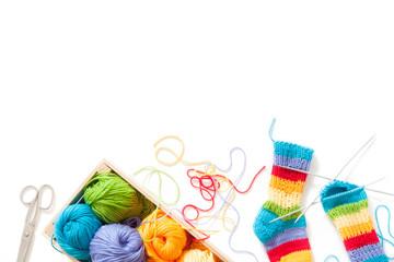 Knitting for children. Bright striped rainbow socks. Colored yarn. White background. Wicker basket.