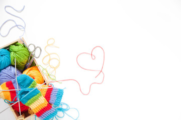 Knitting for children. Bright striped rainbow socks. Colored yarn. White background. Wicker basket. A heart.