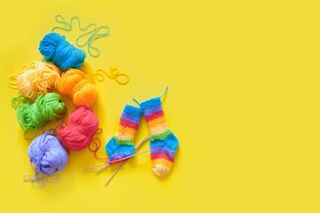 Colored rainbow children's socks. Bright yarn. Yellow background. Knitting with knitting needles.