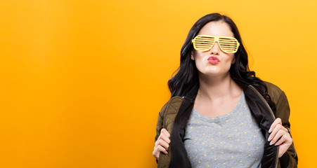 Fashionable woman with attitude in a bomber jacket on a golden yellow background