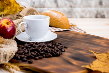 Cup of hot Coffee with toast for Autumn season warm drink. Fall harvest cornucopia. Copy space on wood background.