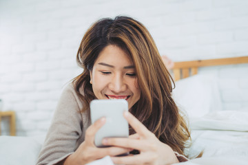 Happy Asian women are using smart phone on the bed in morning. Asian woman in bed checking social apps with smartphone. Smiling woman surfing net with cellphone at home. Mobile addict concept.