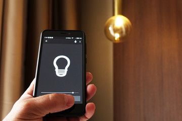 Smart Home: Man Controlling Lights With App On His Phone. electric concept.