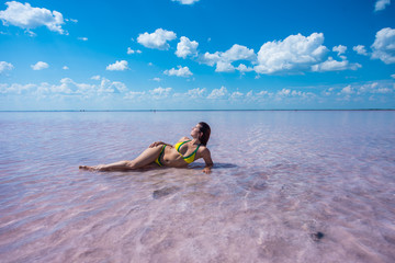 A beautiful red-haired girl in a yellow bikini lies on her side in a pink lake in Altai. Rose lake is a salt Deposit.