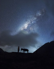Horsemen standing under million stars in sky with his horse near smoking hot volcano Mount bromo at night, Indonesia