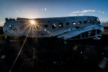 On a summer night in Iceland the sun sets and flares through the window of the Sólheimasandur plane wreck, on the black sand beach where it crashed.