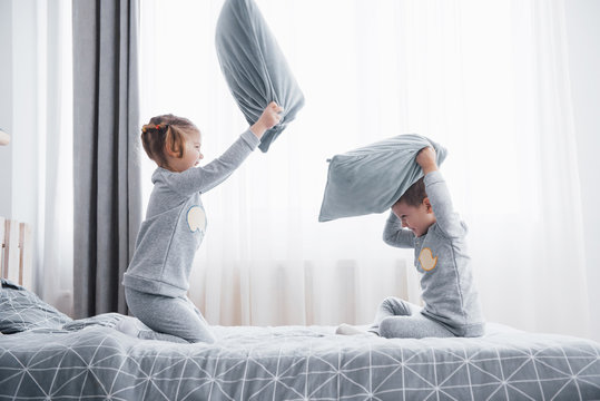 Little boy and girl staged a pillow fight on the bed in the bedroom. Naughty children beat each other pillows. They like that kind of game
