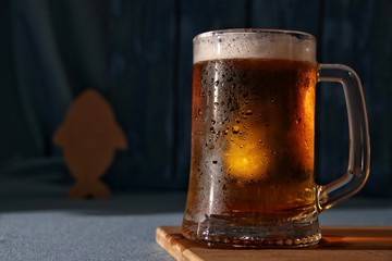 Still life of mug of cold light draft beer on a table with fish on a blue background
