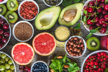 Healthy food selection. Clean eating, fresh organic superfoods, fruits, assortments of berries, nuts and seeds.