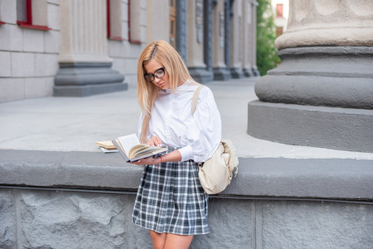 Beautiful student with glasses reading a book at the University.  Cute blonde in a white blouse and a plaid skirt and glasses reading at the school