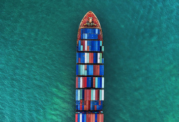 a cargo ship carrying multi-stack of containers in sea aerial view