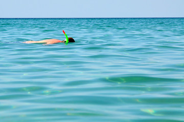 Man swims in a mask with a straw in the sea