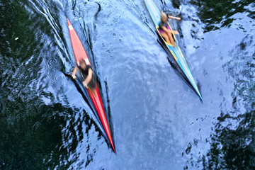 Two kayaks at speed in the water