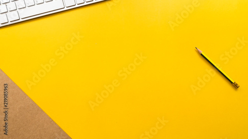 Wall mural keyboard and pencil with brown paper on yellow background business concept