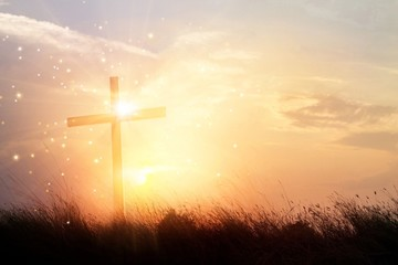Silhouette christianity cross on grass field in sunrise background